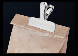 Photo montrant un sac papier kraft replié sur lui même et maintenant ainsi à l'aide d'une pince.